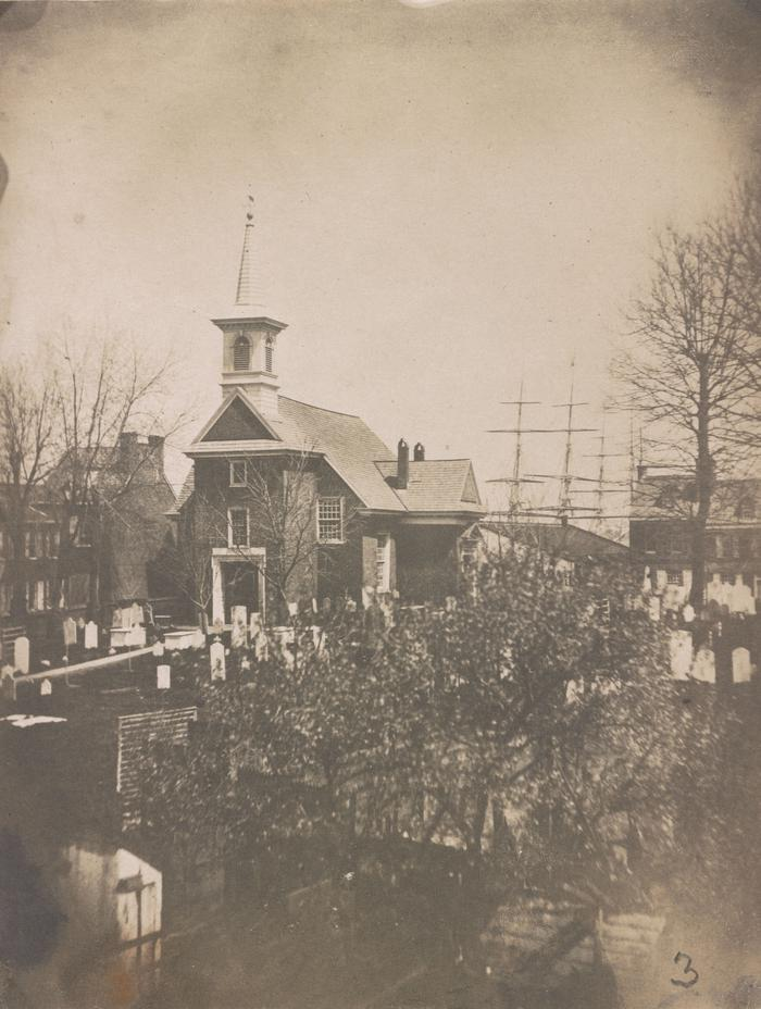 The Gloria Dei Church c.1850This 1850s photograph shows a bird's-eye view of the Gloria Dei Church, with the cemetery in the foreground and the masts of ships visible in the background.