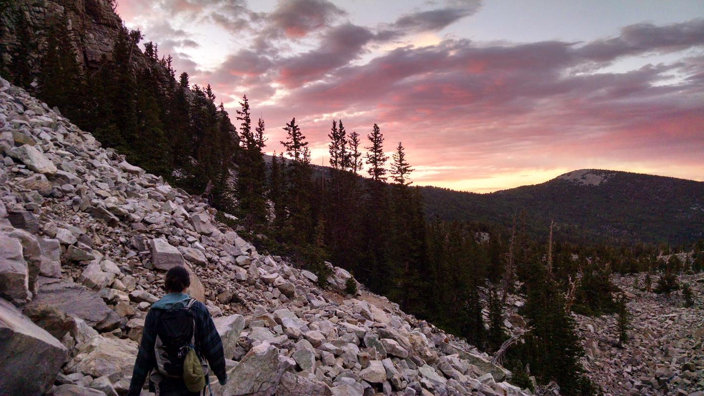 Female hiker on a rocky trail with mountains and sunset in the background.Wheeler Peak Bristlecone Trail