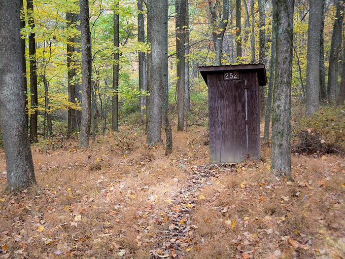 Small enclosed wooden pit toilet building. Surrounded by trees in late fall.A wooden enclosed pit toilet is available for campers at each backcountry Adirondack shelter.