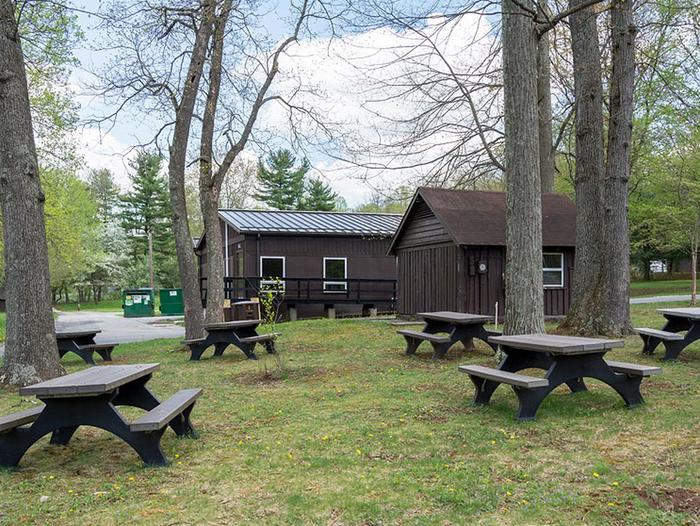 Multiple picnic tables outdoors in grass area on the side of the dining hall facility.  Several large trees shade the picnic area.Beautiful outdoor picnic area is conveniently located next to the camp dining hall.