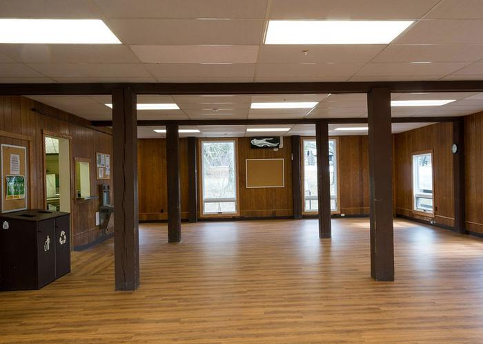 Interior view of dining hall.  Oak colored wood laminate flooring.  Dark brown wooden beams, several large windows, waste/recycle bins and bulletin boards are visible.