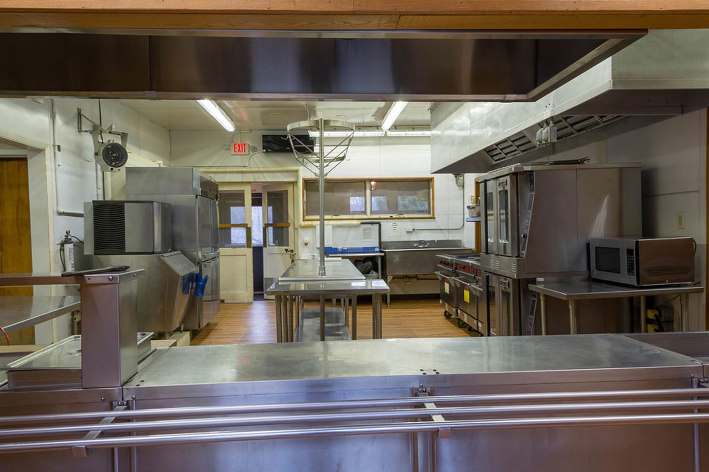 Dining hall front door view of the kitchen. Stainless serving line with 3-well hot food table, prep tables, ice machine, prep refrigerator, 3 ranges, convection oven, microwave and double sink.Dining hall front door view of the kitchen. Stainless serving line with 3-well hot food table, prep tables, ice machine, prep refrigerator, 3 ranges, convection oven, microwave and double sink.  Not visible are 2 large storage areas, 1 small bathroom, walk-in refrigerator, and double freezer.