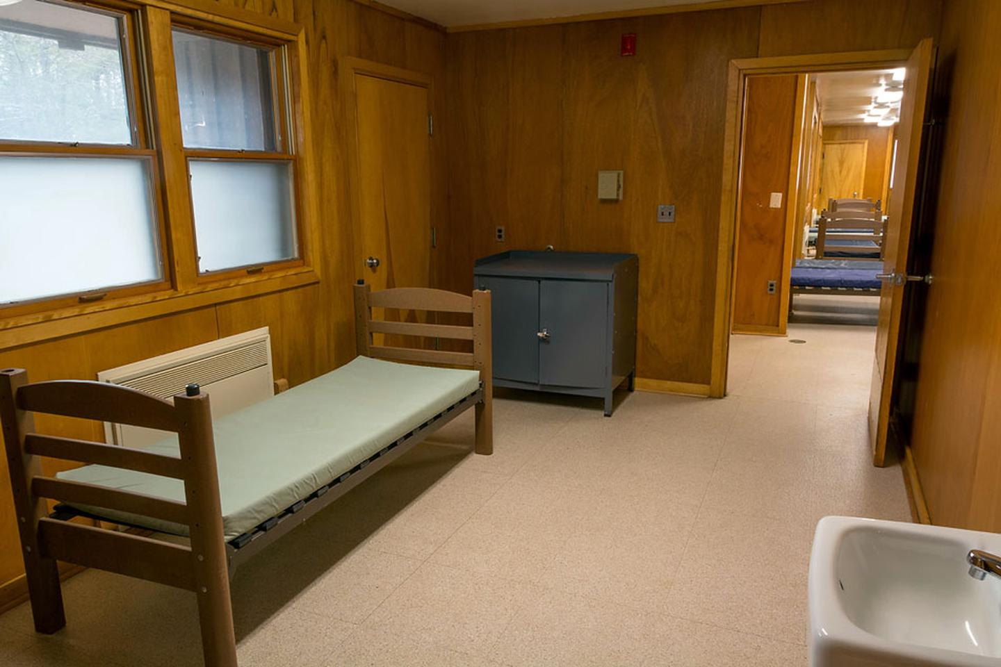 Individual dormitory room, vinyl floor, wooden walls, and one double window. One single bed with vinyl covered mattress, metal storage unit, and small porcelain wall sink.                                                                                There are 2 individual rooms in each of the 4 dormitories.  These rooms contain a single bed with vinyl mattress, a closet, metal storage unit, small sink, wall mirror and wall mounted writing area (not visible)