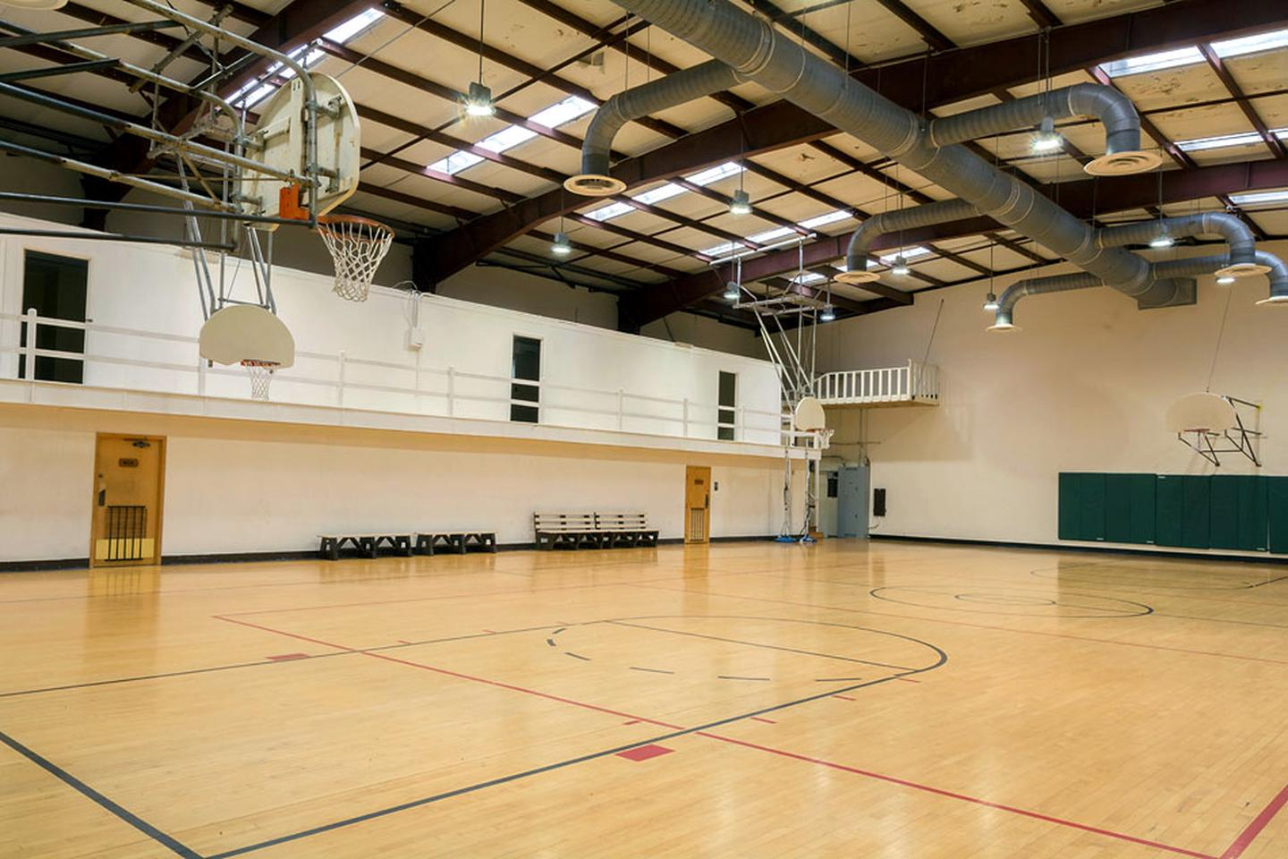 Interior of gym.  Wooden marked basketball court with 4 backboards/nets and 4 benches on sidelines. Metal beam ceiling with skylights. 3 doors visible to upper classrooms. Interior of gym.  Wooden marked basketball court with 4 backboards/nets and 4 benches on sidelines. Metal beam ceiling with skylights. 3 doors visible to upper classrooms. Women's and Men's bathrooms are accessible from the gym court.
