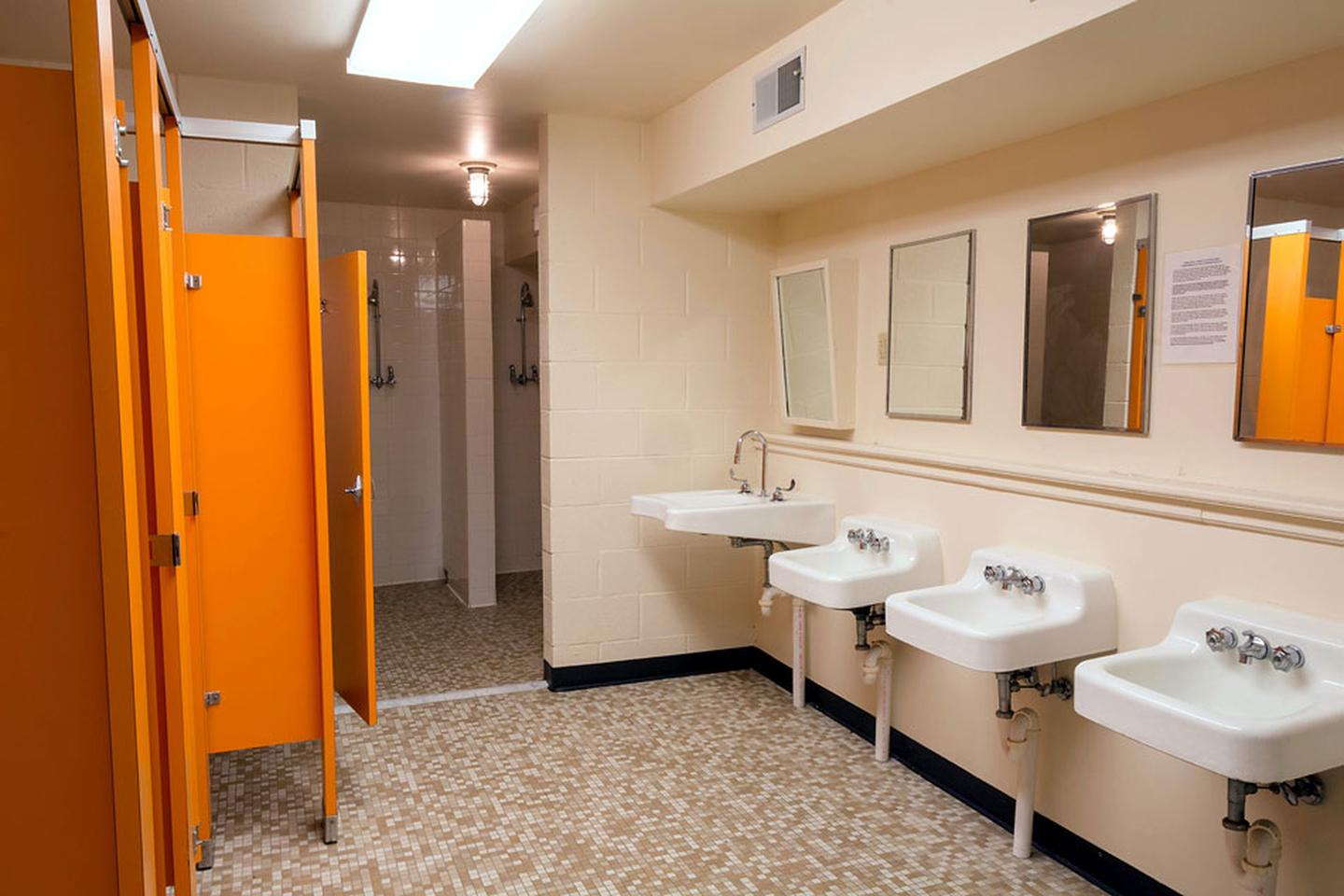 Gym women's bathroom. Tile floor, 4 wall mounted sinks below 4 mirrors. Left side, 4 orange toilet stalls. 4 tile shower stalls which have no door or curtain. The gym women's bathroom has 4 sinks, 4 toilet stalls, 4 mirrors and 5 shower stalls.  Shower stalls have no doors or curtains.  The men's bathroom has 2 urinals, 2 toilet stalls 3 sinks and 5 shower stalls.