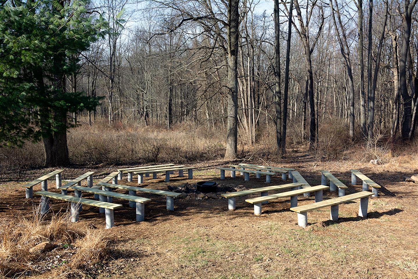 Outdoor fire pit with 18 wooden benches on concrete posts in circular pattern.  Center of circle has a metal fire ring/grill. Winter photo, surrounding trees  have no leaves.The peaceful outdoor fire circle has 18 new wooden benches and a wood shed.