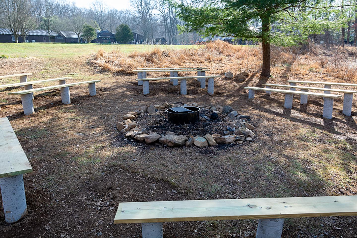 Outdoor fire circle located below athletic field. Metal fire ring/grill surrounded by a stones. Wooden benches on concrete pilings. Rear of dining hall in the backgroundRelax with friends and enjoy nature in the renovated fire circle.  Dry wood is available on site in the new wood shed.