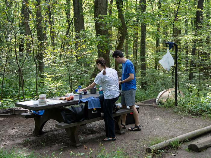 Man and woman standing next to picnic table on wood chip campsite.  On the tent pad behind the campers is a tent.  Waste back hangs from lantern pole.  Site is surrounded by dense forest.The eastern deciduous forest provides privacy and seclusion.