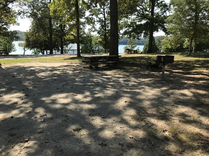 WILLOW GROVE CAMPGROUND SITE #61 GRAVEL TENT PAD WITH SHADE ON SITE AND LAKE VIEW IN BACKGROUNDWILLOW GROVE CAMPGROUND SITE #61