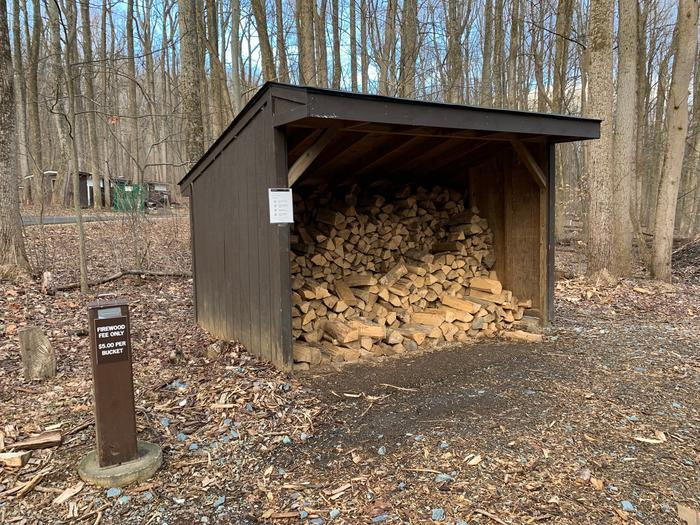 Three-sided wooden shed loaded with split firewood.  Metal firewood donation box is next to shed. Dead leaves and trees without leaves appear in the background.Firewood is available throughout the season to reservation holders.  A requested donation of $5 per bundle assists with campground improvements.