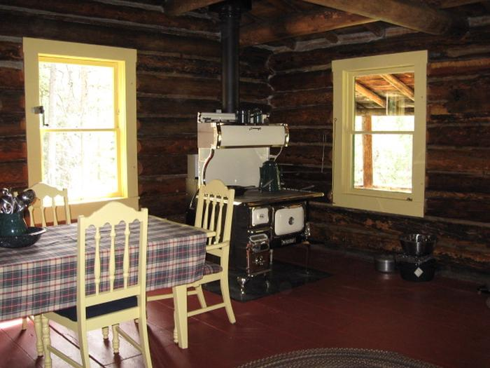 Interior log cabin with dining table, chairs and cook stoveInterior dining/cooking area