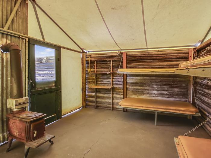 Interior of tent cabinThe Tent Cabin includes two sets pull-down bunk beds for a total of four beds with padding, an interior potbelly wood burning stove for heat, and lighting. While the bunks are padded, sleeping bags and pillows not included.