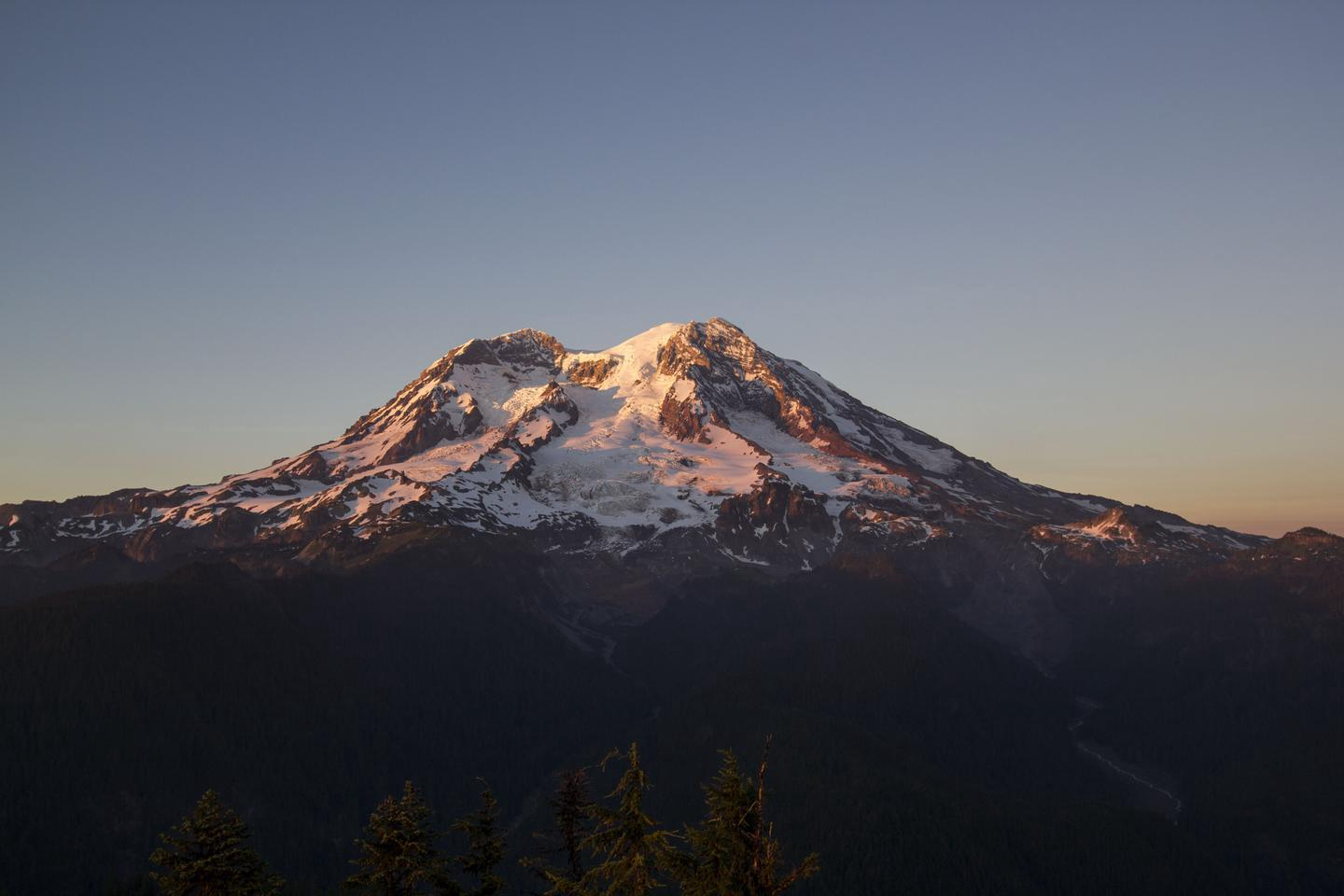 Mount Rainier at sunsetEvery scenic overlook shows a different side of Mount Rainier. Viewed from Gobblers Knob Lookout at sunset, the glaciers covering the mountain turn pink and gold.