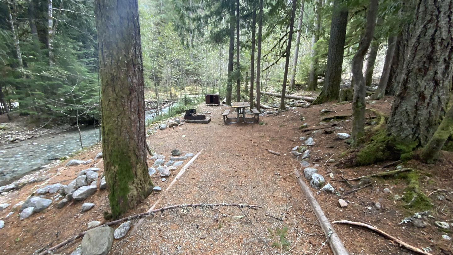 Tent pad, picnic table, fire grate and bear box at campsite. Campsite along the creek.