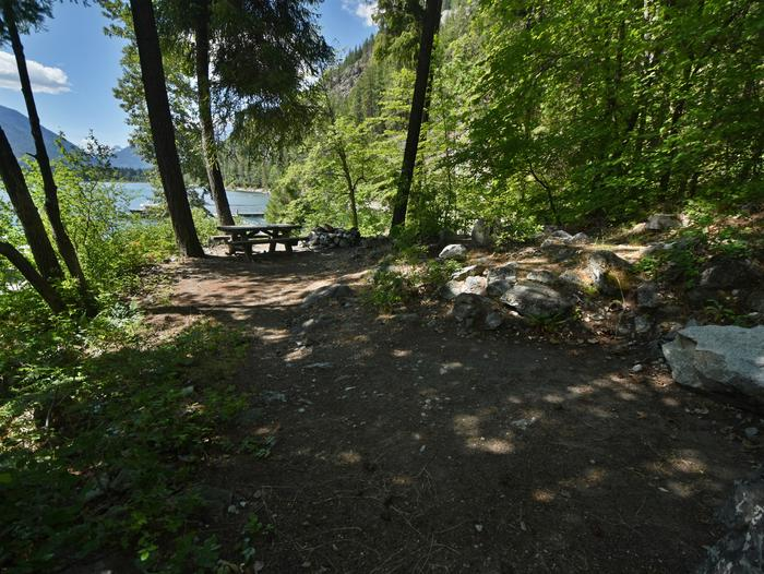A wooded campsite with picnic table and views of a lake and hillsPurple Point Site 3
