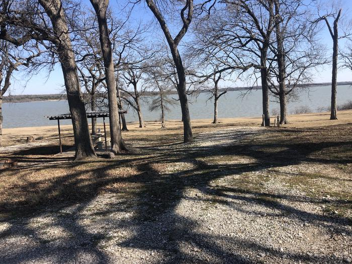 This waterfront site has a metal roof shelter top, picnic table, fire ring, and grill. Water and electric hook ups are available on site at there's room for a standard size RV and one vehicle