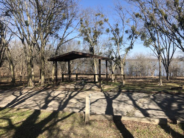 Ample shade available at this wooden shelter Topp site with a picnic table, firing, and grill on site. Water and electric hook ups available and room for a standard two larger size RV with 3+ vehicles