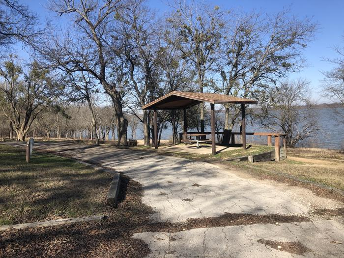 Waterfront site with a wooden shelter top, picnic table, grill, and firing. Water and electric hook ups available and room for a standard to larger size RV with 2+ vehicles
