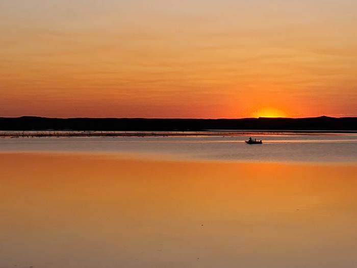 A lone boat out fishing on Lake Oahe at sunset at Hazelton Recreation AreaA lone fisherman out looking for walleye at sunset on Lake Oahe at Hazelton Recreation Area.