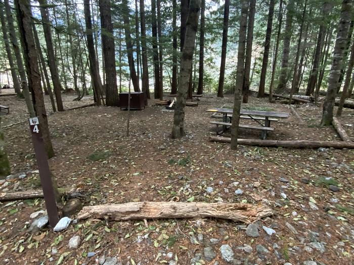Picnic table, bear box, tent pad, and campfire ring set in the trees with Diablo Lake in the distance.View of campsite.