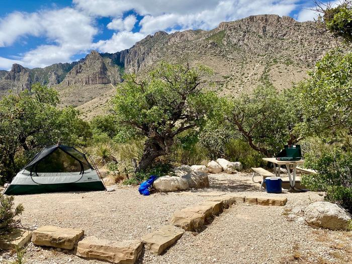 Tent campsite 18 shown with two plus person tent on tent pad, surrounded by small desert trees and vegetation with mountain views in the background.Tent campsite 18 shown with two plus person tent on tent pad a picnic table and mountain views.
