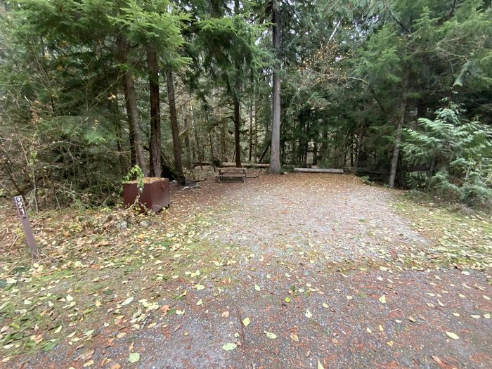 Gravel parking area next to a campsite containing a bear box, campfire ring, and picnic table.View of campsite.