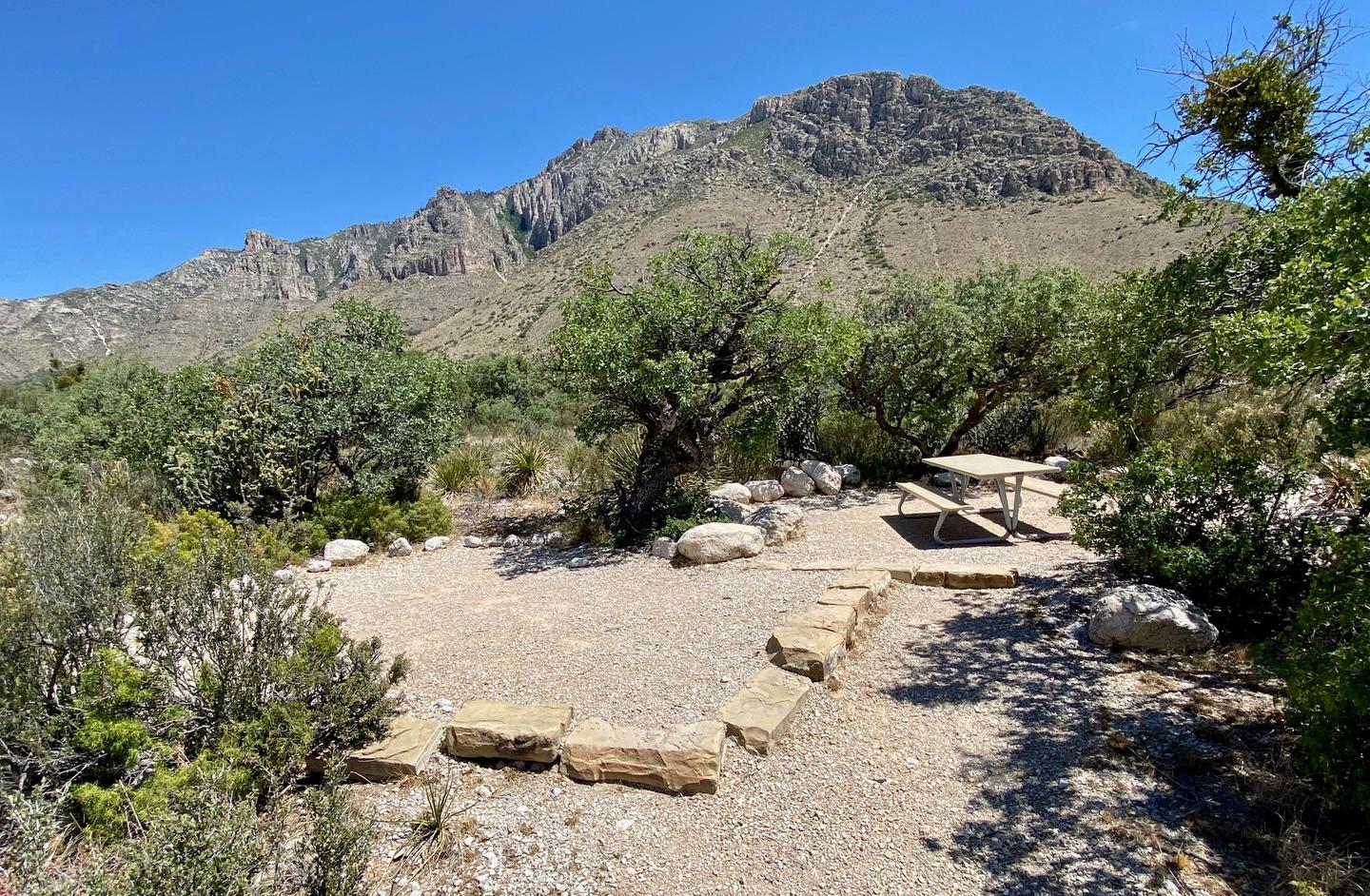 Tent campsite 18, surrounded by desert vegetation and with mountain views in the background.  Tent pad is delineated by large rocks.Tent campsite 18 shown with Hunter Peak in the background.
