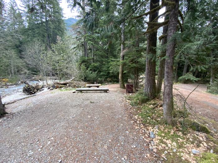 Gravel parking area near a creek and campsite containing a picnic table, campfire ring, and bear box.View of campsite.