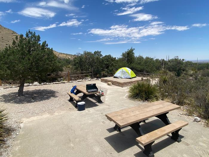 Group site #1 shown with accessible picnic table and tent pad.  An additional picnic table in an open space with small tree and surrounded by desert vegetation.
