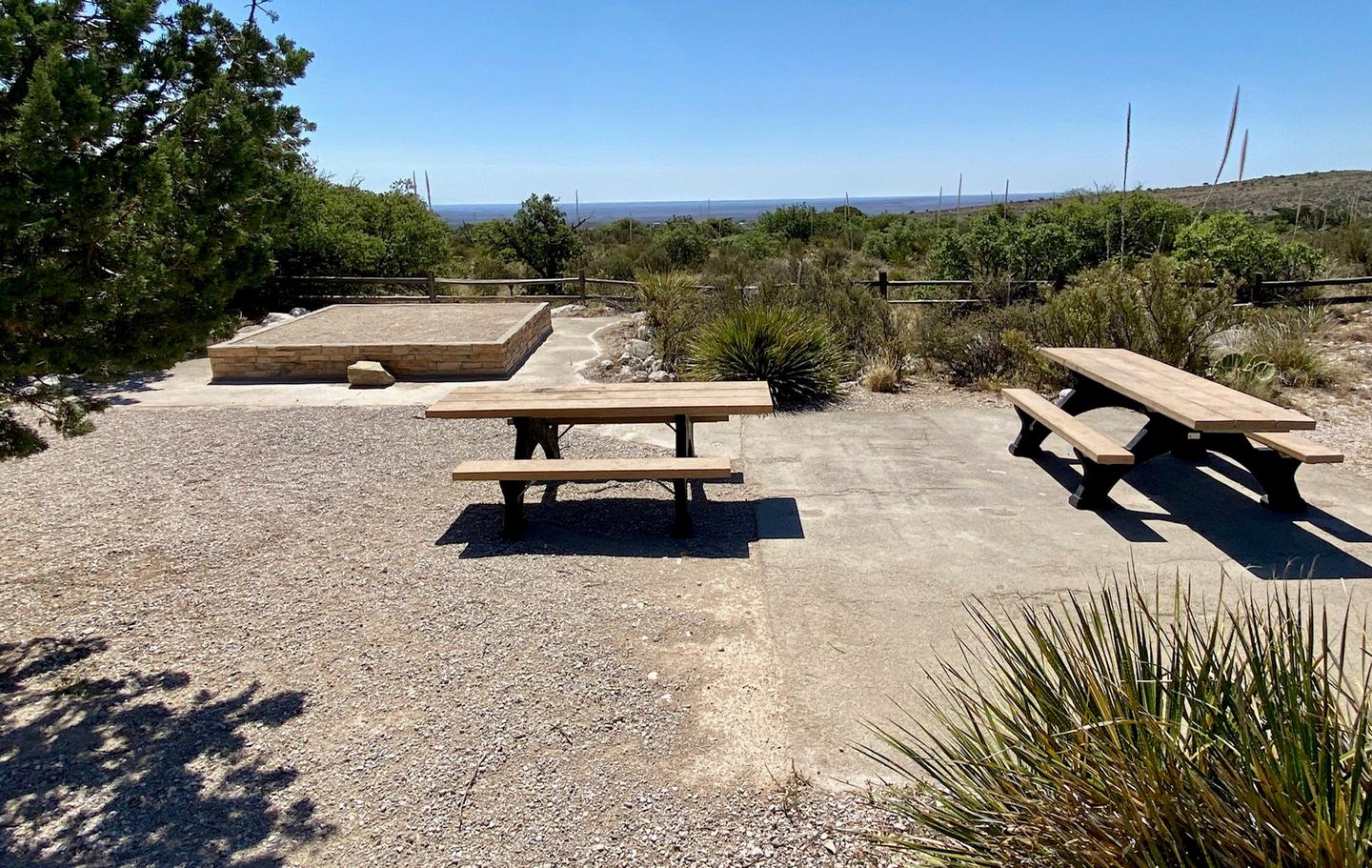 Group site #1 shown with accessible picnic table and tent pad.  An additional picnic table in an open area surrounded by desert vegetation.  View of the Permian Basin in background.Group site #1 shown with two accessible picnic tables and an elevated tent pad.  View of the Permian Basin in background.