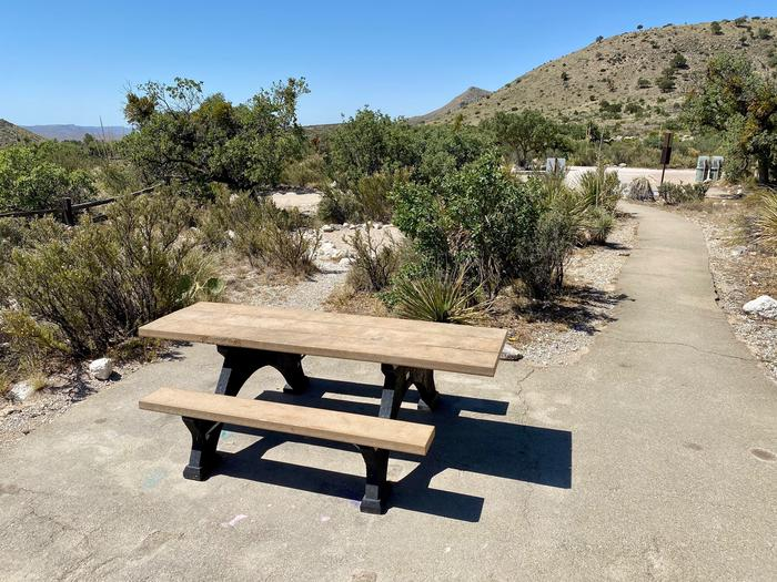Group site #1 showing with accessible table and pave trail leading toward parking space. View of hillside with desert vegetation surrounding site.Group site #1 shown with accessible table and pave trail leading toward parking space.