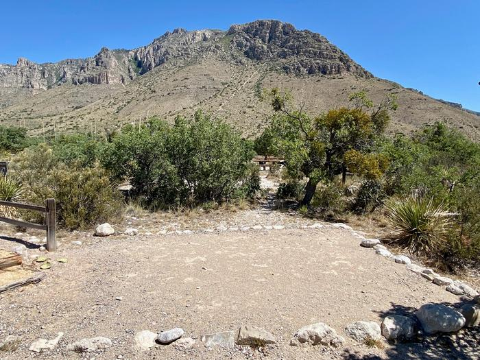 A tent pad is shown in the foreground, this pad is covered in fine crushed gravel and is outlined with large rocks.  There is a view of Hunter Peak shown in the background.  Desert trees and shrubs surround the site.Two of  the four tent pads in group site #1.  Hunter Peak is visible in the background.