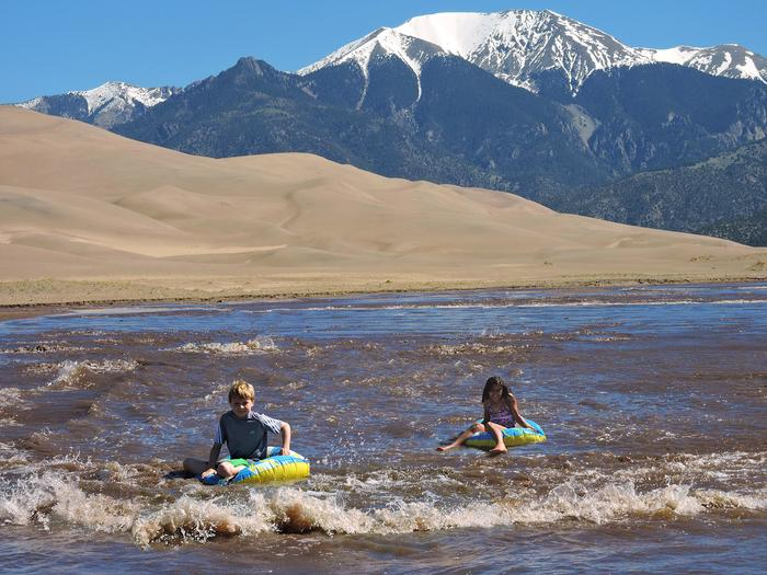 Children Floating Medano CreekMedano Creek is a popular beach environment at the base of the Great Sand Dunes. It flows seasonally April through June, with peak flow in late May.