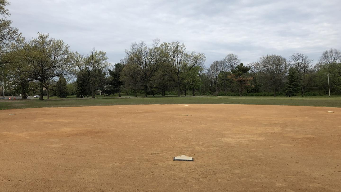 A view of field S10 from the backstop. The image shows an infield with bases and an outfield surrounded by trees.East Potomac Park Softball Fields