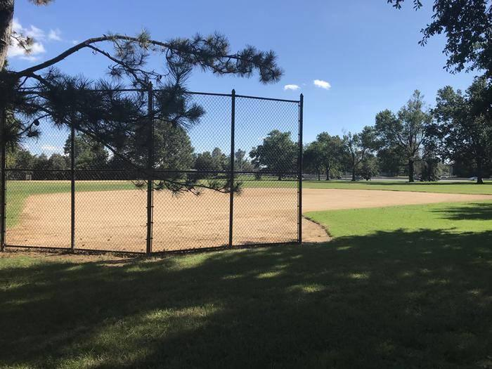 Field S9 as seen from behind the backstop. The image shows a fenced backstop, a clay infield, and a grassy outfield.Field S9