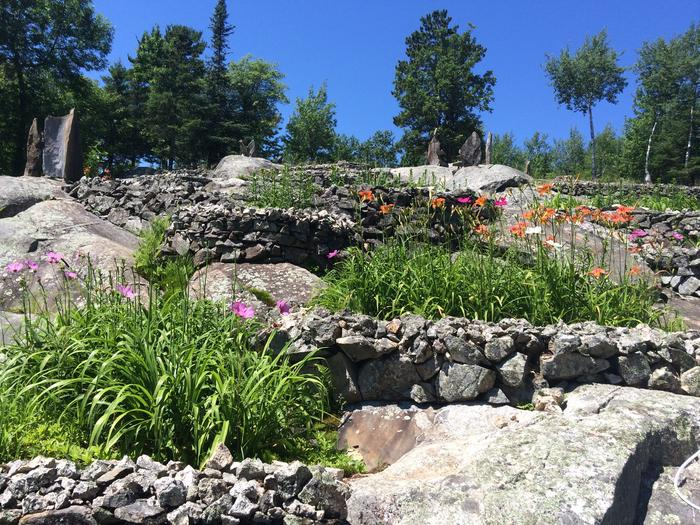 Three small colorful flower beds tucked into cervices of the large granite outcropping.