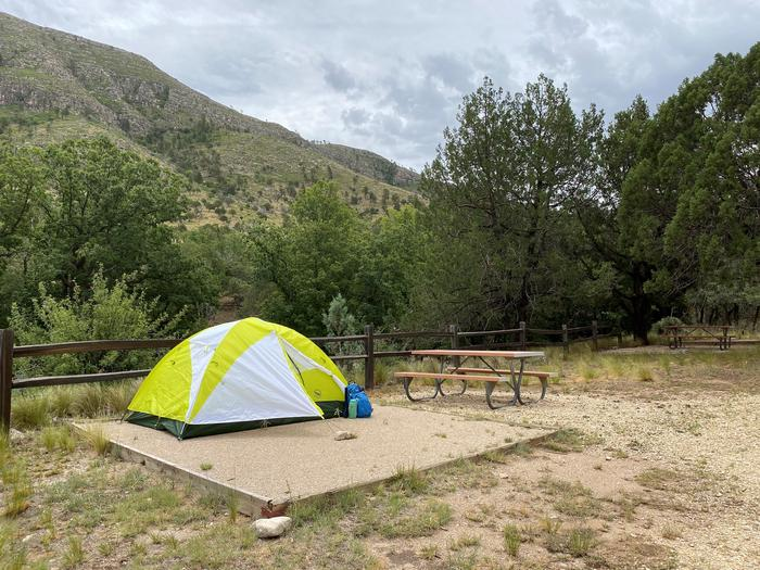 Dog Canyon tent campsite with mountain views, a tent pad with a two-person tent displayed and picnic table.Dog Canyon tent campsite with mountain views