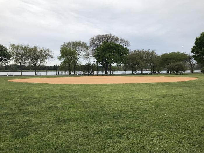 A view of field S3, featuring an outfield, infield, and backstop. In the background, the Potomac River is visible.A view of field S3 with the Potomac River in the background.