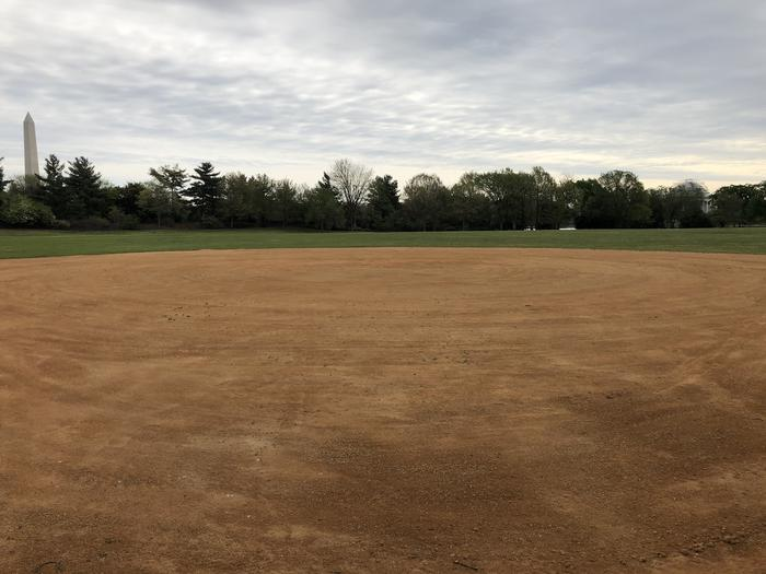 A view of field S4 from the infield. Beyond the infield, a grassy outfield is bordered by trees with views of the Washington Monument and Thomas Jefferson Memorial.Field S4 as seen from the infield.