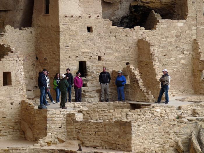 Visitors touring a large, ancient, stone-masonry villageCliff Palace