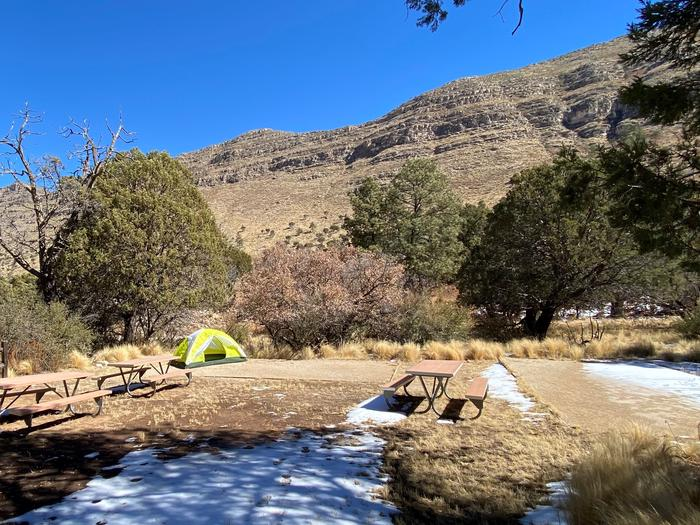 Dog Canyon Group site has two large tent pads and three picnic tables.  Photo shows one 2-person tent on a tent pad.  The site is surrounded by mature trees and has mountain views.Dog Canyon Group Campsite