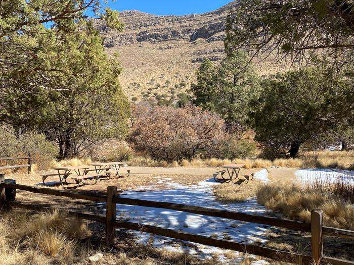The group campsite in Dog Canyon shown with trees and mountains surrounding the site, two large tent pads and three picnic tables.  The site has rustic fencing along two sides.Group campsite, located in Dog Canyon campground.