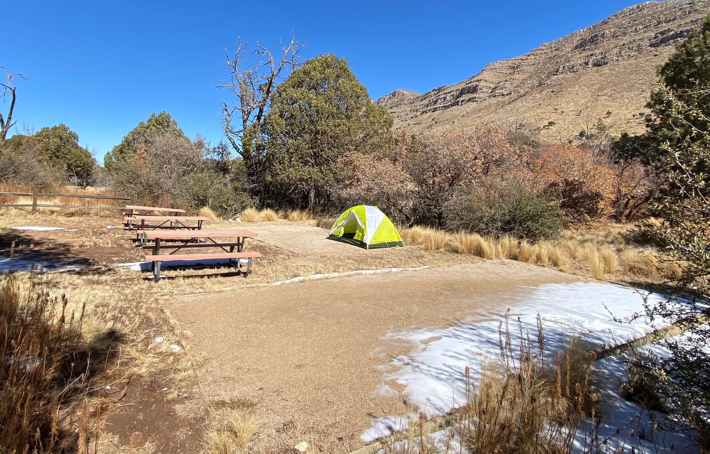 The group campsite located in Dog Canyon is shown with one 2-person tent on a tent pad.  This view is from the right side of the campsite and shows mountains in the background.Group campsite in Dog Canyon with surrounding trees and mountains.