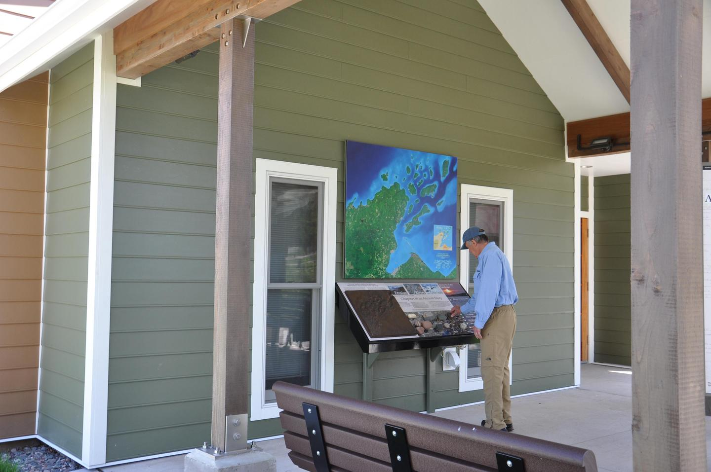 Wall map with touch and audio exhibits under patio.Beneath a large map of the park, touch a 3-D model of the islands, rocks from around the park, and listen to stories of the park.