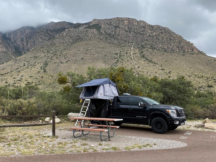 Pine Springs RV Site with view of Hunter Peak in background.  This site has a paved parking spot with picnic table.  Photo shows a full size truck with a roof top tent setup.RV campsite in Pine Springs campground. Hunter Peak with rain clouds as a backdrop.