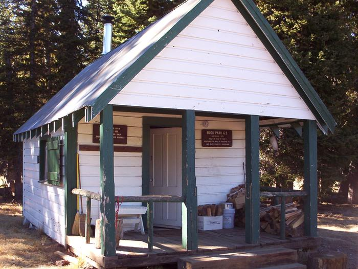 Front of white and green cabinBuck Park Cabin - porch and exterior