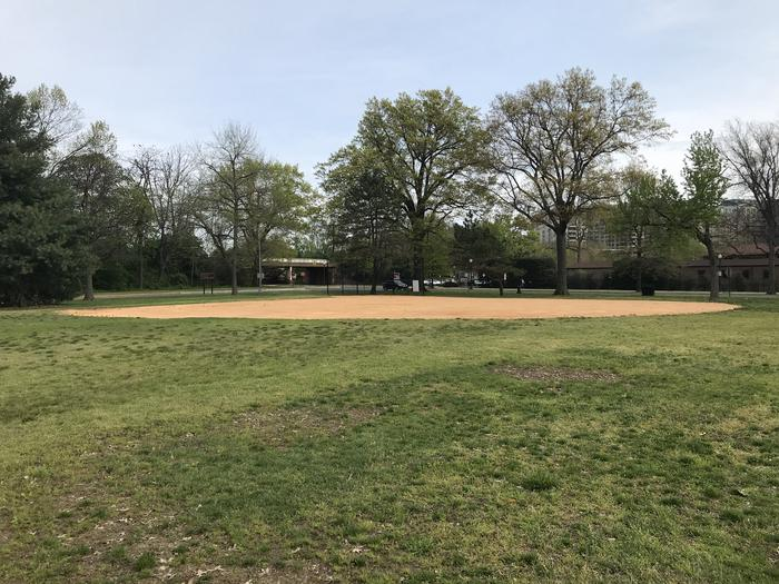 The photo shows field S9 from the outfield. There is a backstop, infield, and grassy area. There are scattered trees in the background.Field S9