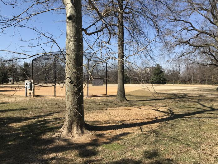 The photo shows field S10 with trees behind a backstop, infield, and grassy outfield. There are scattered trees in the background.Field S10