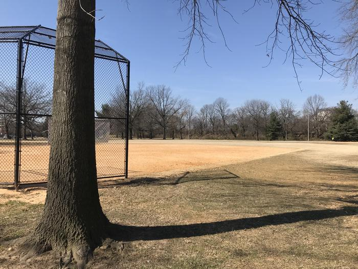 The photo shows field S10 with a tree behind a backstop, infield, and grassy outfield. There are scattered trees in the background.Field S10