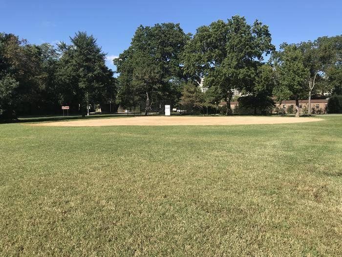 A view of softball field S9 from the outfield. The image shows a clay infield, backstop, and trees in the background.Field S9